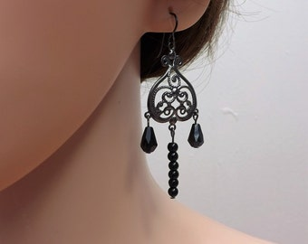 Black chandelier earrings with glass beads and niobium wires.