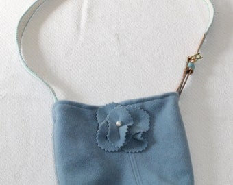 Small rectangular shaped blue cashmere bag with woven belt strap and blue silk lining.