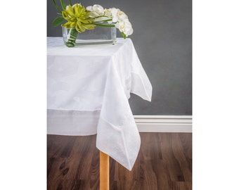 White table cloth , tone on tone brush design with a solid border . Custom tablecloth