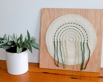 Circular Weaving, Woven Wall Hanging in Natural White and Greens. 12 inch by 12 inch.