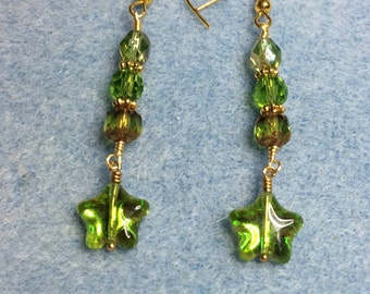 Green metallic star dangle earrings adorned with green Czech glass beads.