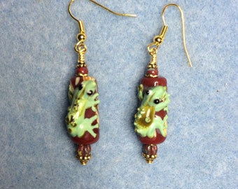 Red and green lampwork lizard bead earrings adorned with dark red Picasso Czech glass beads.