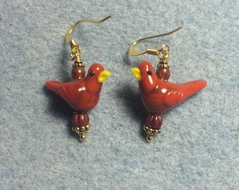 Opaque burnt orange lampwork songbird earrings adorned with burnt orange Czech glass beads.