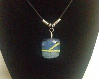 Blue sky with clouds of white & strikes of yellow fused glass pendant on black cord.