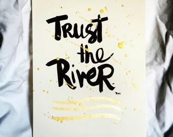 """Trust the River hand lettered 9"""" x 12"""" brush script on beautiful watercolor paper with black and gold ink."""
