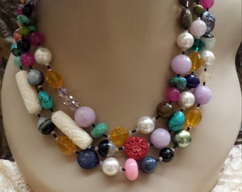 three strand beaded necklace with variety of stones