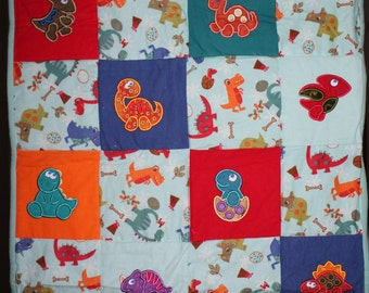 Flannel baby blanket with appliqued dinosaurs