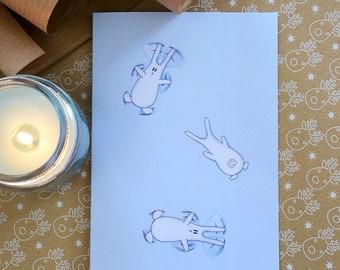 Snow bunnies. Cute bunnies making snow angels Christmas greeting card. Blue bunnies card.