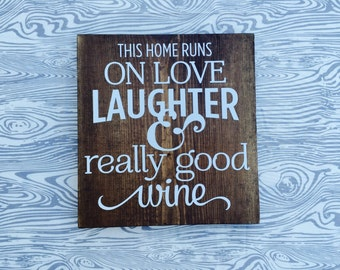 This home runs on love, laughter and really good wine sign