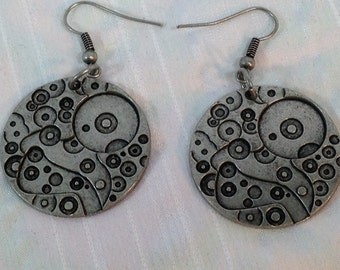Steampunk earrings with an imprinted charm. Charm is imprinted with gears.