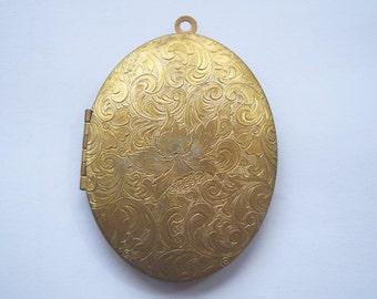 Large floral motif brass locket.