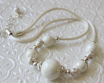 Sterling silver and porcelain cream-colored beads on knotted satin cord necklace