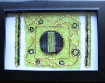 Beaded design in green and black using vintage Lucite coat button, framed