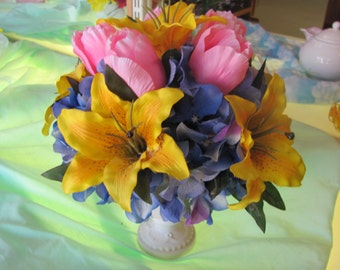 cream colored ceramic pot with yellow lillies, pink tuplips and blue hyrdragea