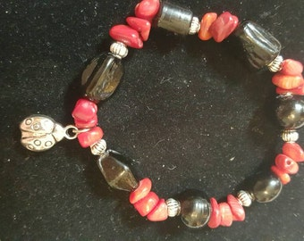 Red and black stretch bracelet with ladybug charm