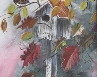 Birdhouse amid fall leaves