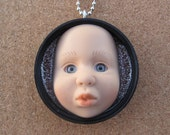 The Pouter -upcycled  baby doll bottle cap pendant