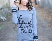 She Believed She Could So She Did. Off the Shoulder Long Sleeved Long Heathered Tee, Sport Striped Wrists- 6 tee colors .  Made in the USA.