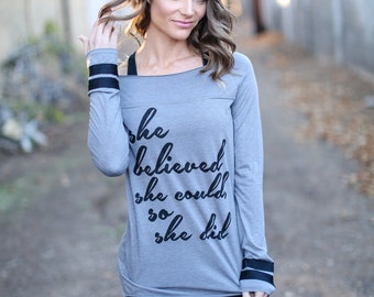 She Believed She Could So She Did. Off the Shoulder Long Sleeved Long Heathered Tee, Sport Striped Wrists- 6 tee colors. Women's Quote Shirt