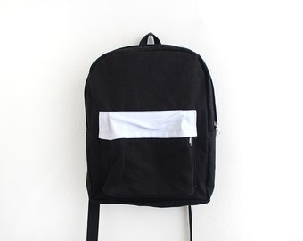 Black canvas backpack with white pouch.