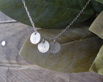 initials etched on tiny nickel discs