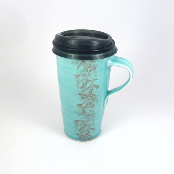 Aquamarine glazed porcelain travel mug with scrolling leaves pattern and translucent smoke silicone lid