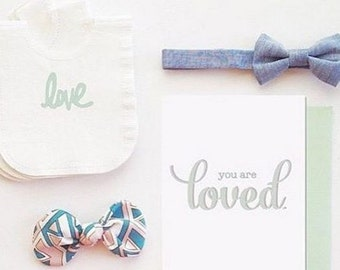 Pack of 30 baby shower napkins in any color with LOVE in white.  Each one shaped like a baby snap shirt or a baby bib. Lots of colors!
