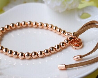 MK Rose Gold plated beaded bracelet on leather thong.