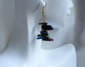 Irregular shaped flat beads rotate and reflect blue, purple, green and gold segments as they dangle on these earrings