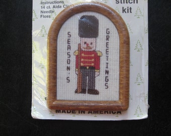 Season's Greetings. Small cross stitch kit. Tin Soldier in arched wood look frame with easel back. NOS/deadstock