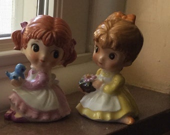 A Pair of Vintage Maruri Masterpiece Bone China Little Girls - one holding a blue bird, the other holding flowers