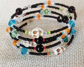 Skull Bead Memory Wire Bracelet - inspired by Dia de Los Muertos. Black seed beads with lots of colorful accent beads.