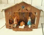 Vintage Nativity set cardboard chalkware figures faux woodgrain illustrated background 1950s