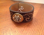 Tan and black leather bracelet with locket