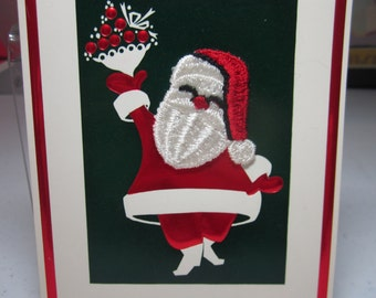 Vintage 1950's Henri Fayette christmas card embossed shiny red and green colors santa claus w/ fabric face holds holly berry bouquet