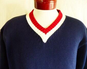 vintage 90's Tommy Hilfiger solid navy blue cotton jersey knit tennis sweater red white stripe trim v-neck collar embroidered griffin crest