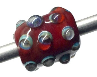 Lampwork barrel shaped focal bead in a rich burgundy red with ivory and blue dots