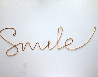 "Soft cursive ""Smile"" wall phrase colourful aluminium wire"