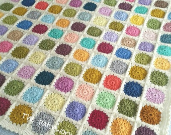 Hand made crocheted blanket featuring bright coloured starburst flowers on a cream background 115x115cm / 45x45 inches