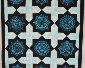Quilted wall hanging or lap quilt. Machine pieced and quilted in beautiful spiraled turquoise and blacks