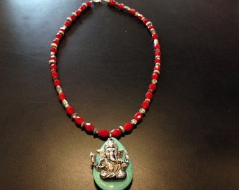 A Buddah necklace with turquoise & red earrings.