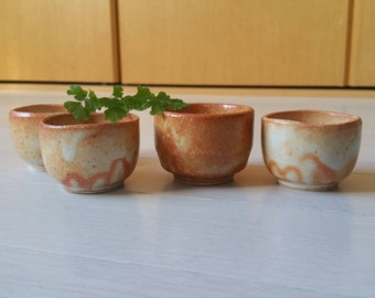 Japanese pottery, coral sake cups.