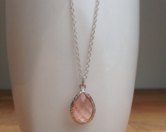 Silver and light peach/ orange framed crystal necklace.