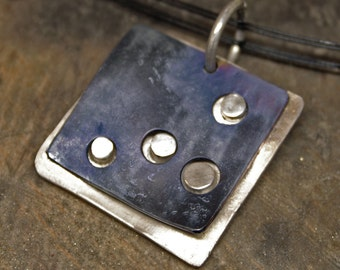 Pure silver pendant with overlapping anodized titanium plate