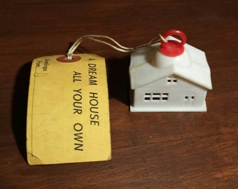 Quirky vintage plastic house, postage tag included, post WWI. Ornament.