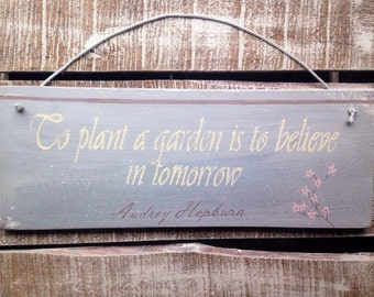 audrey hepburn quote. rustic sign. to plant a garden is to believe in tomorrow.