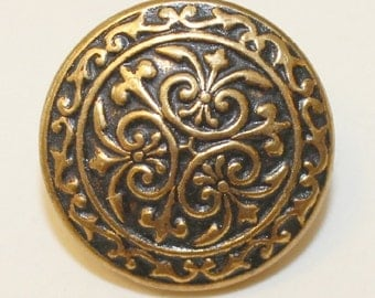 Vintage gold metal button with swirl design inprinted on black backgound