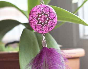 Bright fuchsia mandala with crystals and a feather