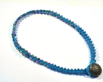 Necklace of wax cord and glass beads with a knot as closure