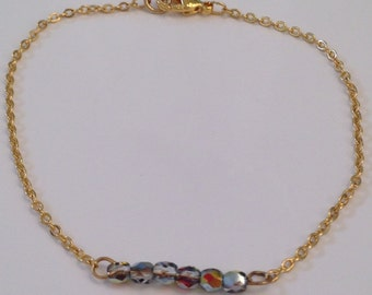 Delicate gold chain bracelet with gray bead bar